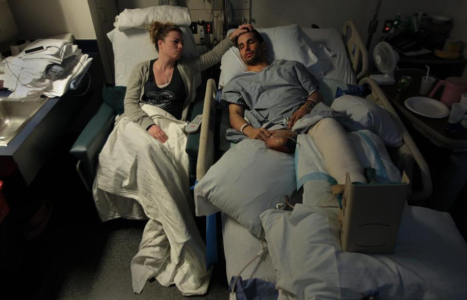 Jen Regan, fiancee of Marc Fucarile, who lost a leg in the Boston Marathon bombing, stroked his forehead as he lay asleep in his hospital bed in Massachusetts General Hospital following his eighth surgery.